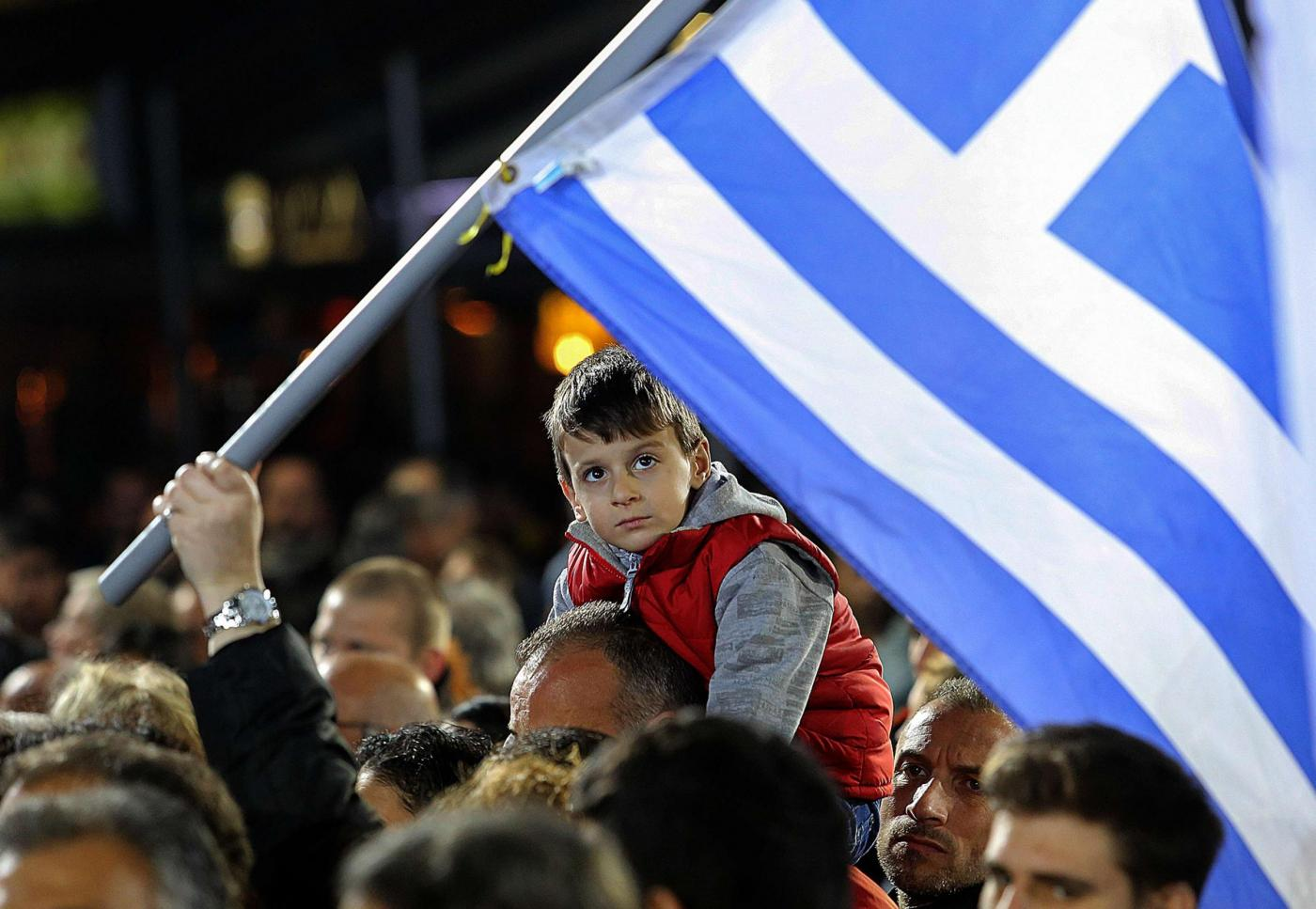 A child sitting on his father's shoulders attends a campaign rally by opposition leader and head of radical leftist Syriza party Alexis Tsipras in Heraklion, on the island of Crete