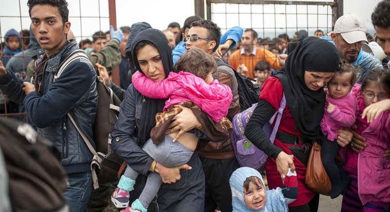 Macedonian police officers control a crowd of migrants and refugees as they prepare to enter a camp after crossing the Greek border into Macedonia near Gevgelija on October 8, 2015. Macedonia is a key transit country in the Balkans migration route into the EU, with thousands of asylum seekers and migrants - many of them from Syria, Afghanistan, Iraq and Somalia - entering the country every day. AFP PHOTO / ROBERT ATANASOVSKI 4638#Agencia AFP