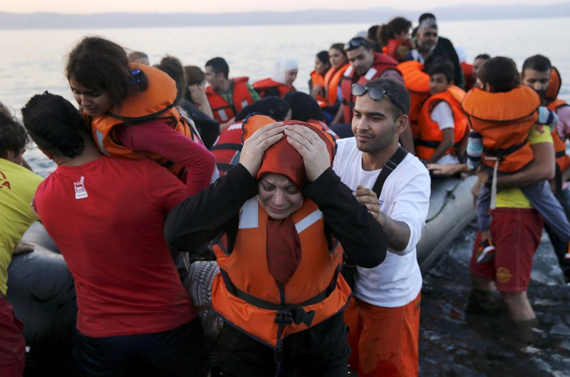 A Syrian refugee woman reacts as she and family members jump off a overcrowded dinghy after landing safely on the Greek island of Lesbos after crossing a part of the Aegean Sea from the Turkish coast (seen in the background), September 19, 2015. A girl believed to be five years died on Saturday and 13 other migrants were feared lost overboard after their boat sank in choppy seas off the Greek island of Lesbos, the Greek coastguard said. A second, exhausted group of around 40 people reached the island in a small boat following a traumatic journey from Turkey, having paddled through the night with their hands across 10 kilometers (six miles) of ocean after their engine failed. Hundreds of thousands of mainly Syrian refugees have braved the short but precarious crossing from Turkey to Greece's eastern islands this year, mainly in flimsy and overcrowded inflatable boats. REUTERS/Yannis Behrakis  4637#Agencia Reuters